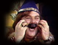 Mazeppa in his blue hat and robe wiht a mustached made of electrical tape scratching his cheeks in an early episode of The Uncanny Film Festival and Camp Meeting.