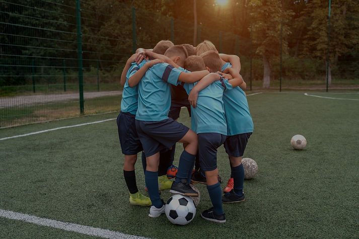 children-soccer-team-coach-hugs-each-oth
