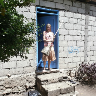 Outside my one room cement home that had no electricity, running water or toilet facilities. I lived directly among the local people, experiencing life as they do which some days, even involved having no food to eat.