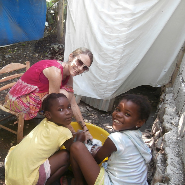 Doing my laundry in a bucket with some beautiful helpers ... the hearts of the Haitian people are like no other!!