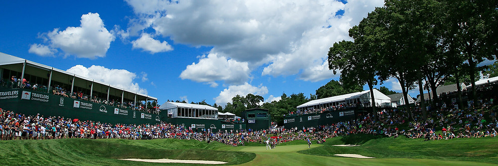 A view of the course during a previous Traveler's Championship. Crowds are gathered around a hole as a player makes his swing.