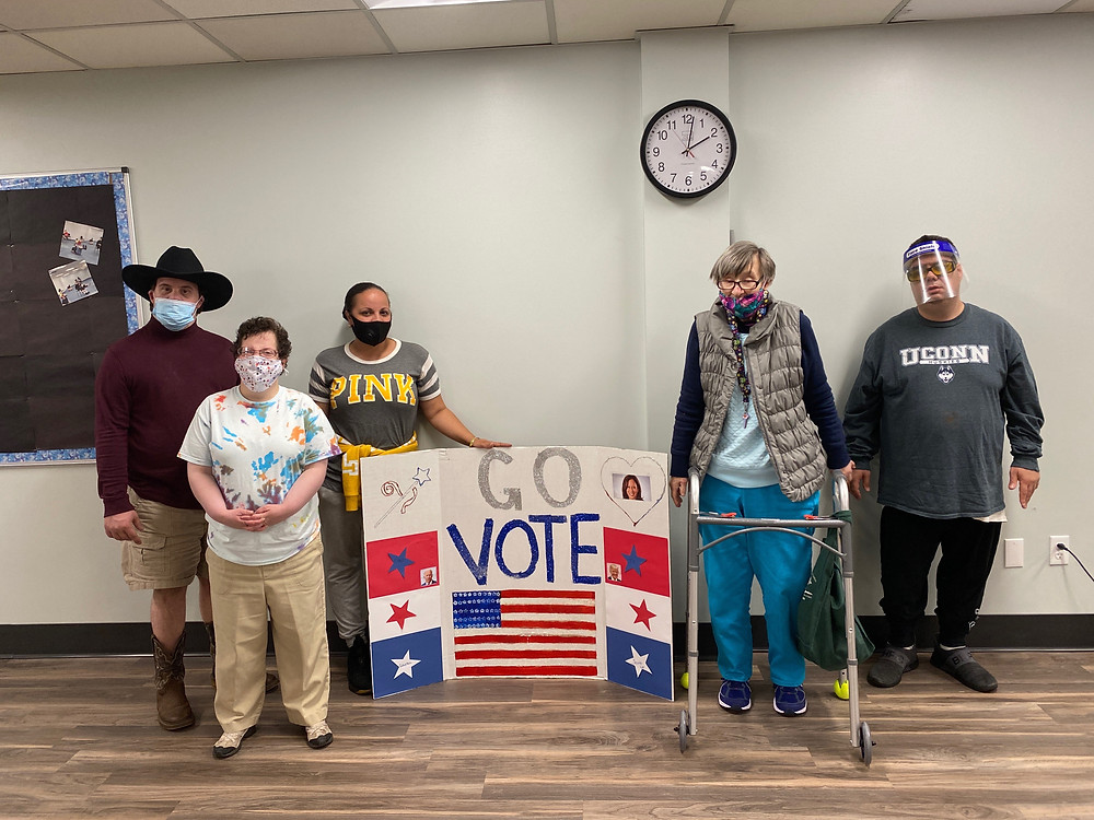 """Individuals stand around a tri-fold poster decorated in American colors with an American flag that reads """"Go Vote""""."""