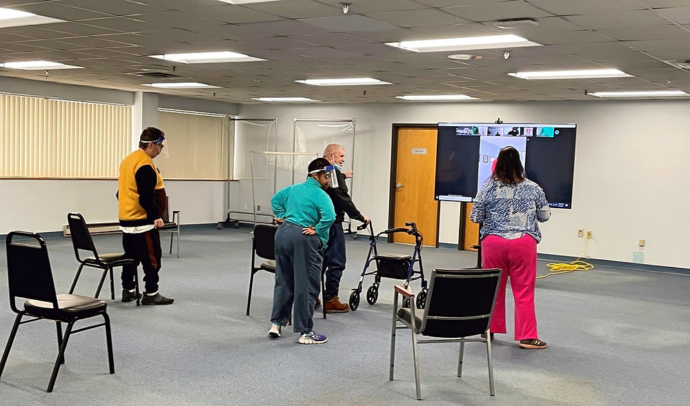 Four people in a large room are dancing in front of a large TV connected to a virtual instructor and friends who join the program from home.