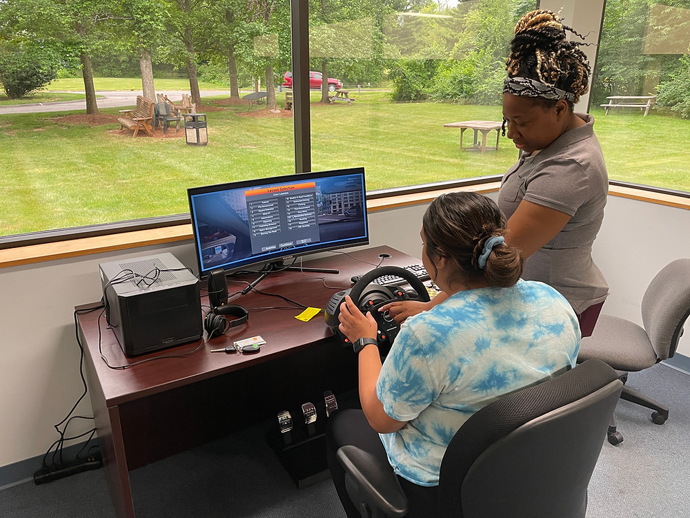Two women are at a desk with a steering wheel and screen. One is behind the wheel while the other teaches them how to use it.