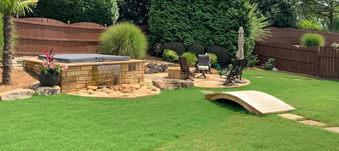 Installation of wooden bridge to stone patio and stonework jacuzzi and plants