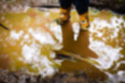 Child playing in a muddy puddle outside
