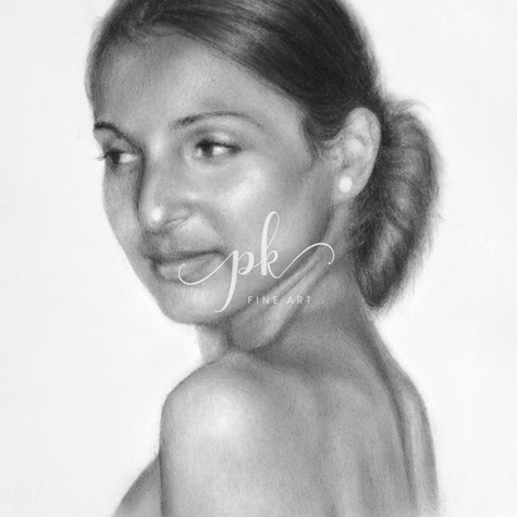 A charcoal and graphite portrait drawing of an Indian woman with her hair in a bun