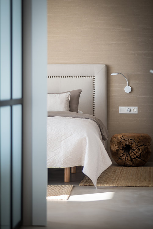 Bedroom of Avitan Villa: a bed with a white bedspread against a cappuccino-colored wall.