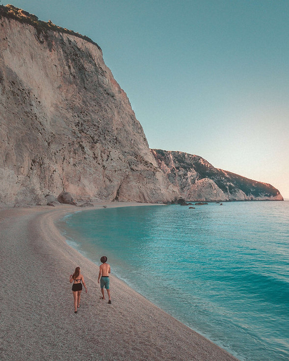A guy in a hat and a girl are walking along the ocean.