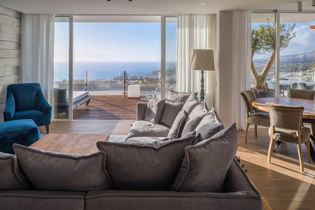 A living room of Villa Avitan Gray with ocean view. There are huge grey sofa, blue chair, wood table and terrace with ocean view.