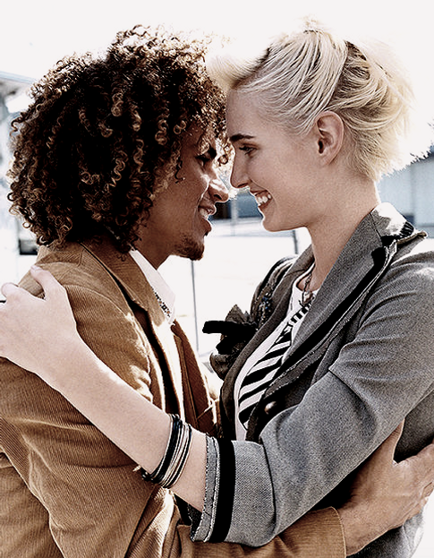 A black guy with curly hair hugs a girl with white short hair