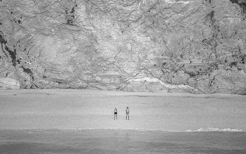 A couple stands on the shore and looks at the ocean. There are mountains behind them