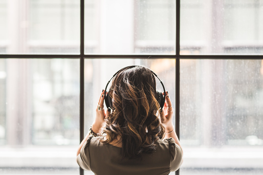 Girl listening to podcast with headphones in front of a large window while it rains outside