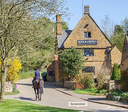 Outside of the Rose and Crown with a horse on the road