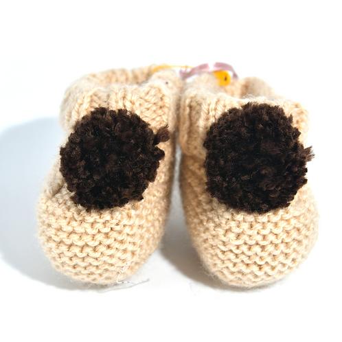 Chaussons de naissance en crochet beiges à pompons