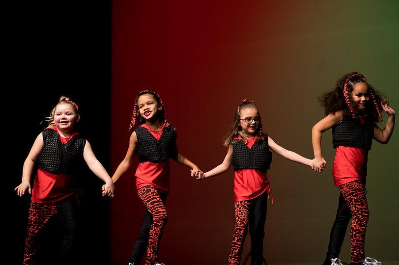 four-dancers-holding-hands-smiling
