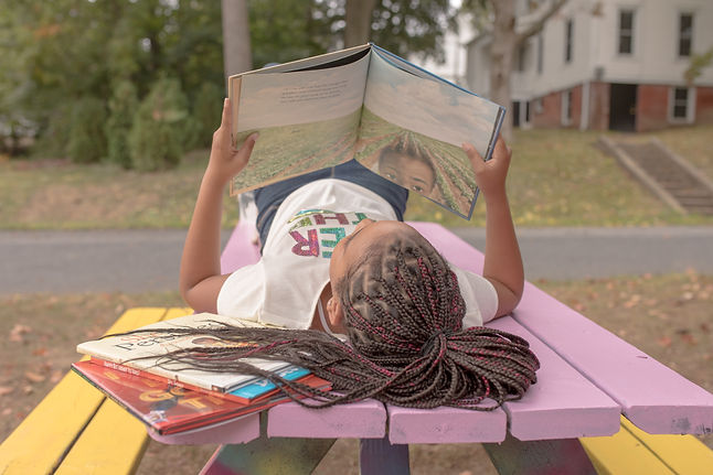 Aaliyah Hall reading on bench.jpg