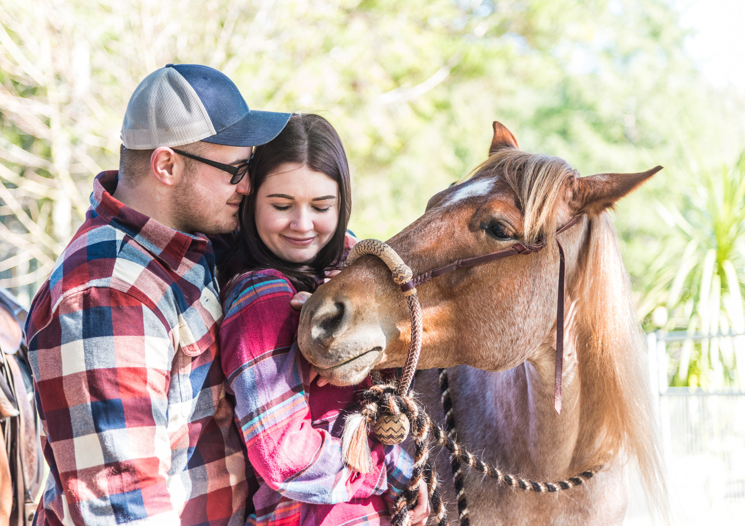 couple pose wit horse