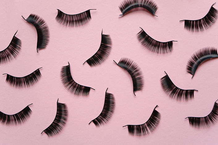 Black false lashes strips on pink backgr
