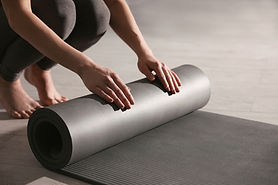 bigstock-Woman-Rolling-Yoga-Mat-In-Stud-