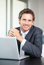 Empresário sorrindo em notebook
