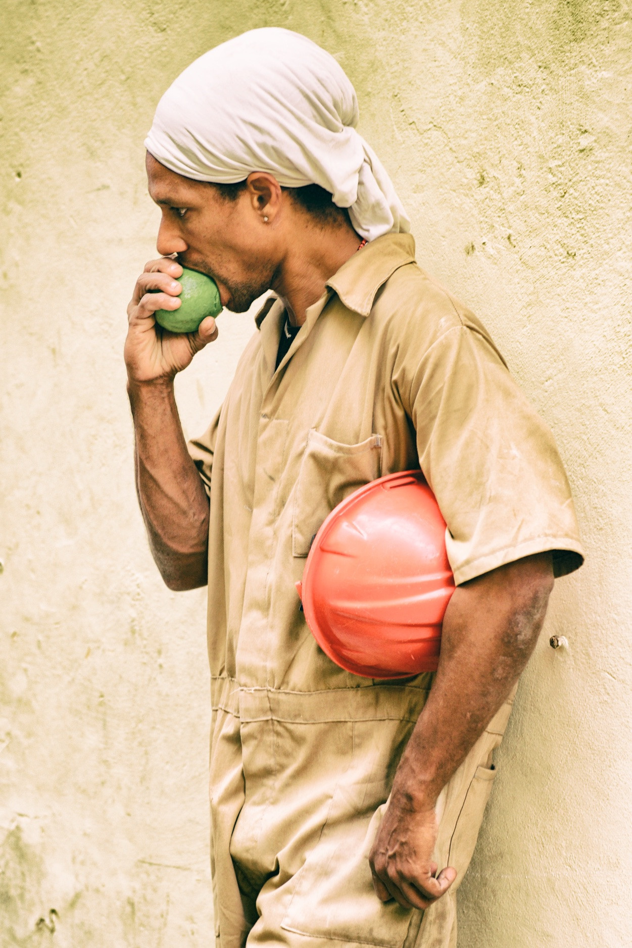 Construction worker eating a green apple
