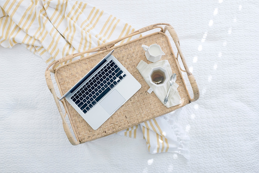 laptop on bed with tea next to it on Zo Connected website to describe blog post checlist for small business owners