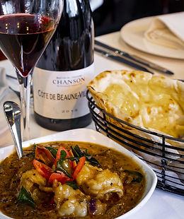 Indian food with prawn curry, garlic naan and red wine.