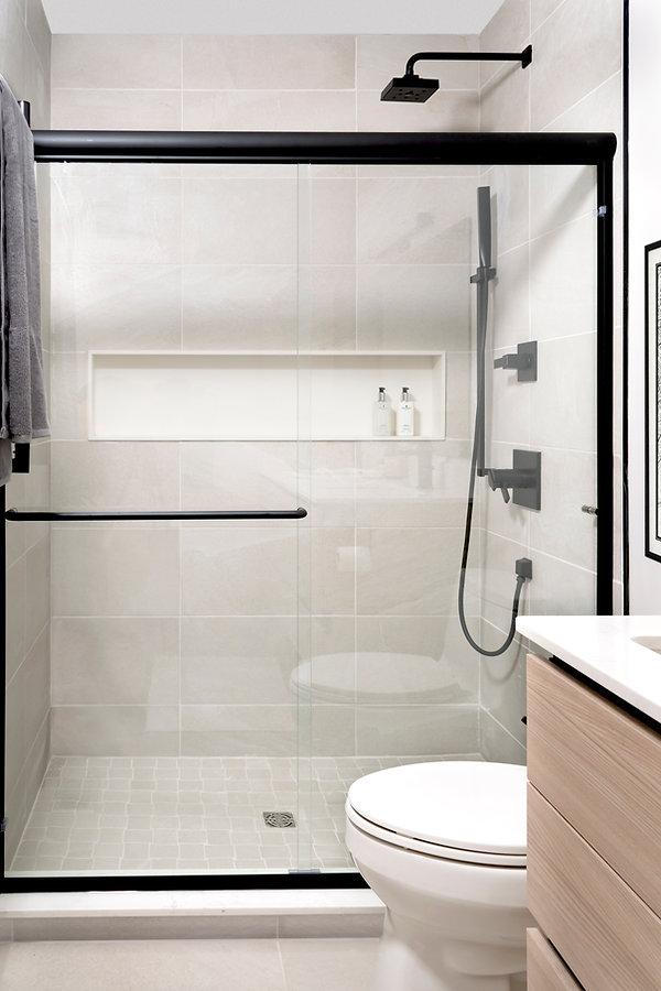 Agalite shower door, Milestone North porcelain tile, black hardware, Eclipse cabinetry Natural elm, Kohler Verticyl lavatory, Kohler Santa Rosa Toilet, Nu-Heat