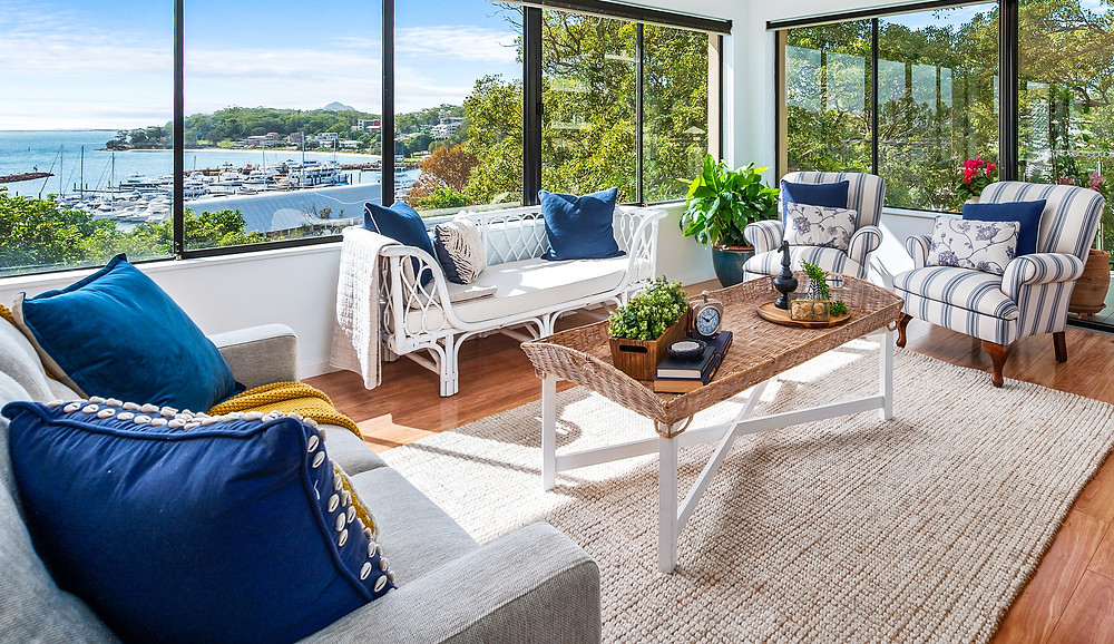 Coastal luxury in Port Stephens by Home Property Styling, using linen lounge, cane two seater, coffee table, rug and accent chairs