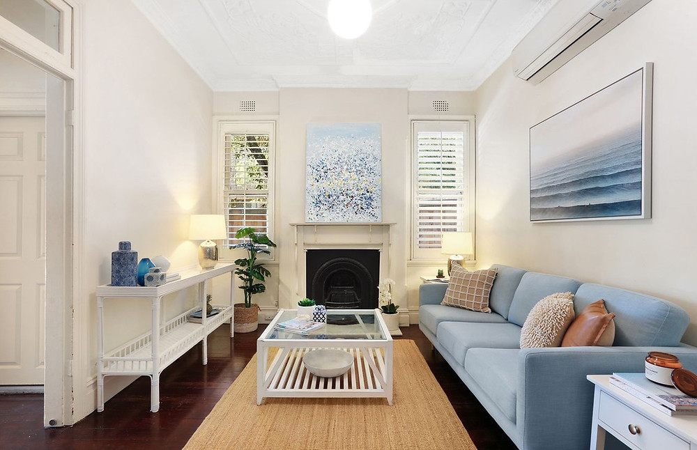 After photo of loungeroom after staging by Home Property Styling. Using beach chic themes with soft blues, timber and cane furniture