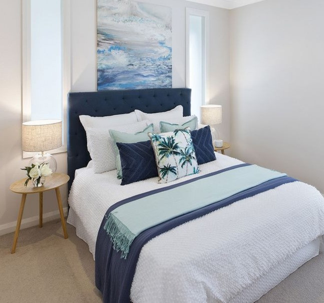 Blues and greens in a bedroom setting, including side tables, lamps and artwork