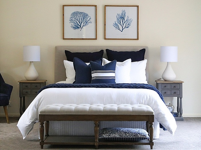 Elegant master bedroom with headboard, elegant side tables and ottoman
