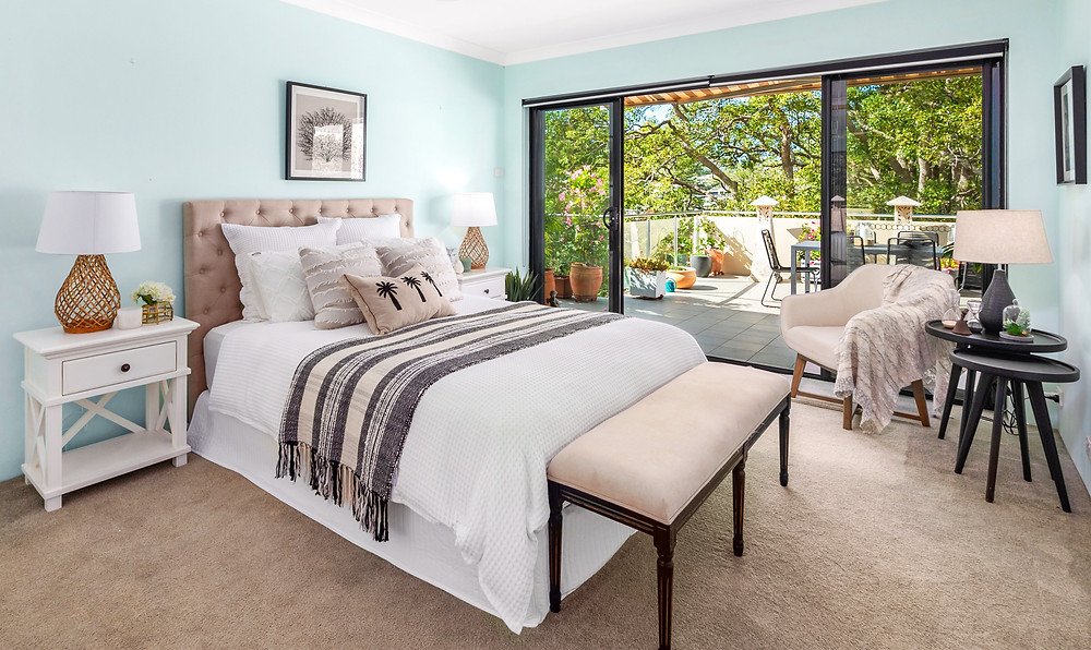 Queen bed with beige bedhead, hampton style side tables and benchseat by Home Property Styling