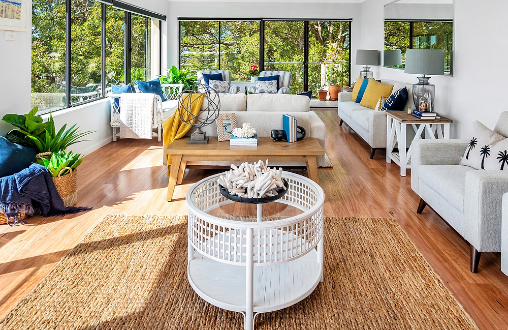 Jute rug, cane coffee table, lounge suite, console and homewares in a beautifully styled penthouse Port Stephens by Home Property Styling