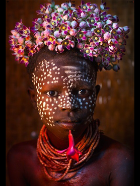 A young child with flower decoration on his head in Korcho, Omo Valley, Ethiopia.