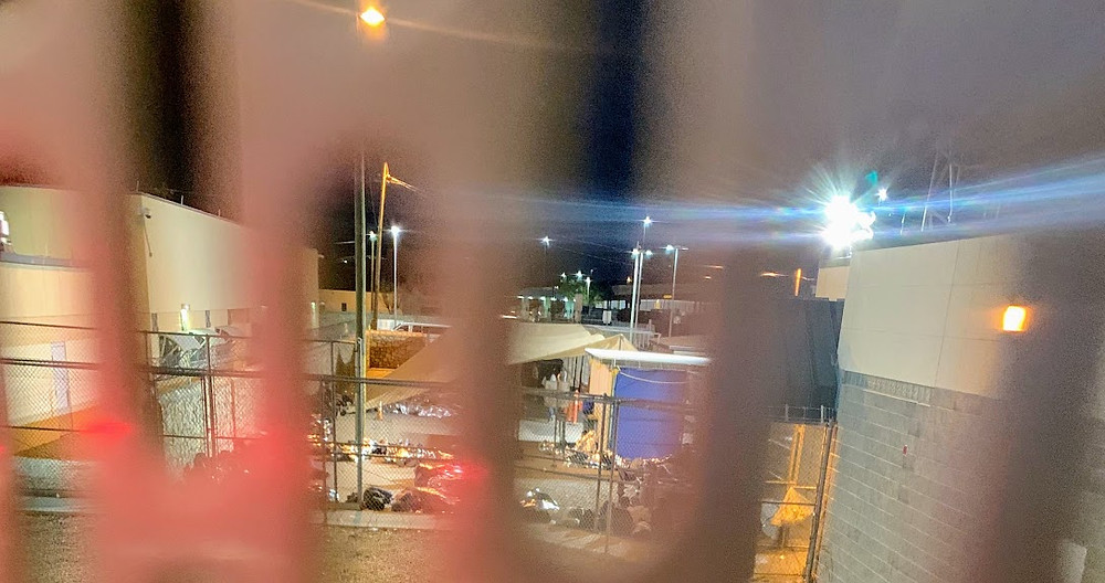 Peering through bars at sleeping migrants