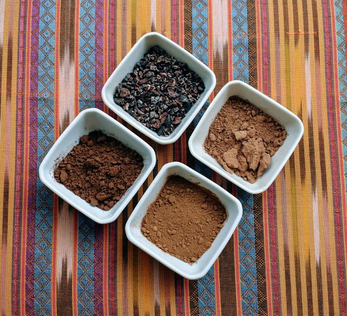 A sampling of cacao nibs, raw cacao powder, cocoa powder, and carob powder.