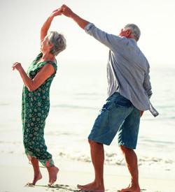 Senior couple dancing at beach on sunny
