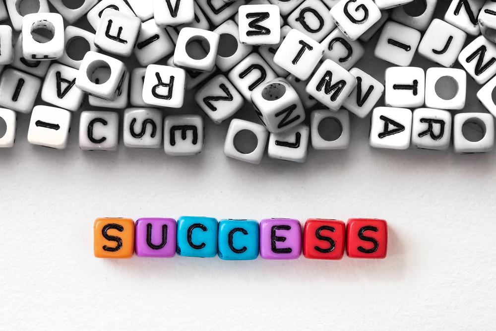 The word success is spelled out in color in front of a pile of black and white letters.