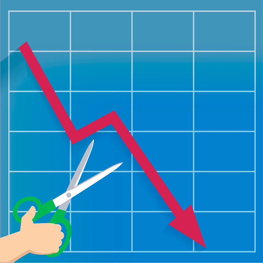 A hand with a pair of scissors enters a graph to cut a line that is decreasing.