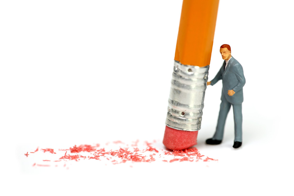 A businessman erases his language-learning mistakes with a huge pencil.