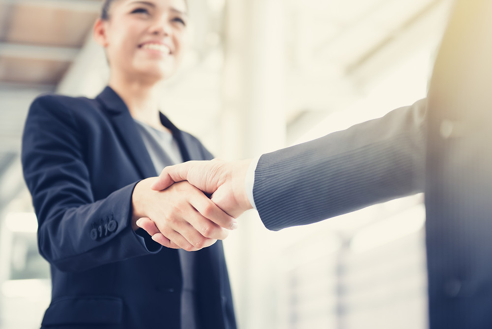 A businesswoman arrives at her job interview and shakes hands with the hiring manager.