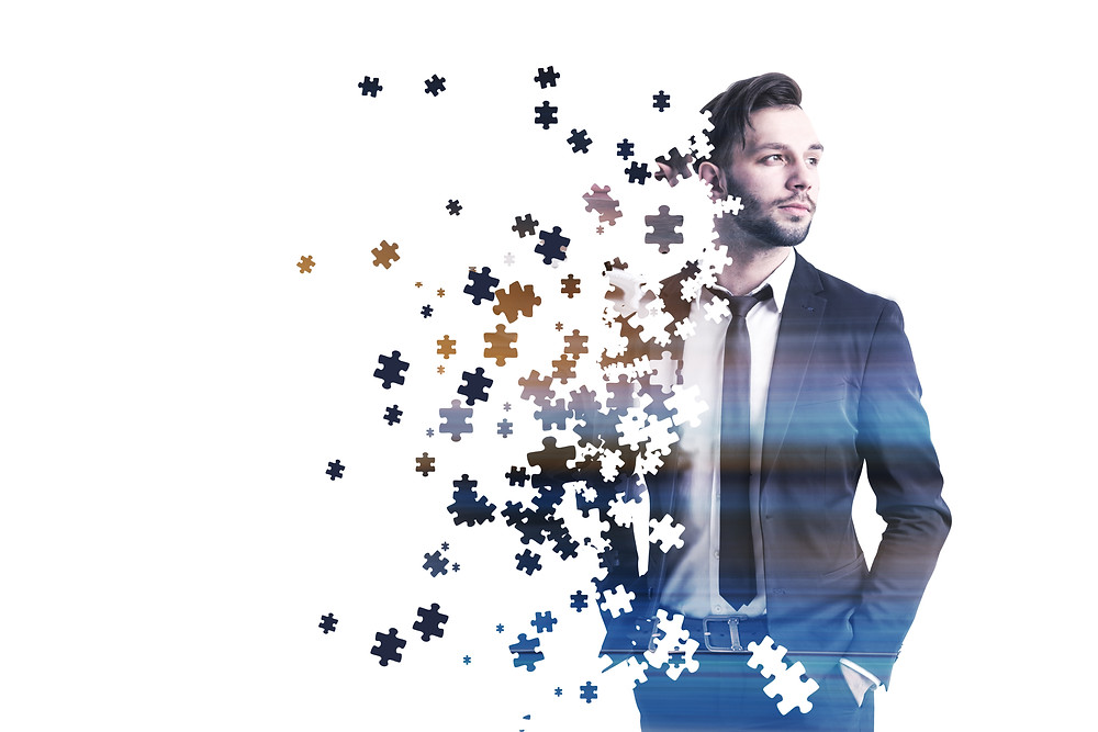 Puzzle pieces are scattered on the left side of the image that slowly fade into the portrait of a businessman.