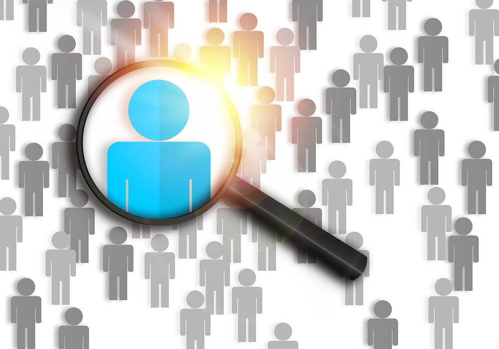 A magnifying glass highlights the perfect job candidate in a crowd.