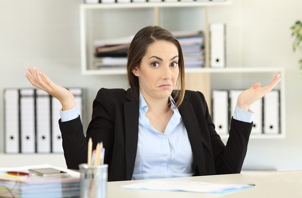 A businesswoman shrugs her shoulders during her job interview.