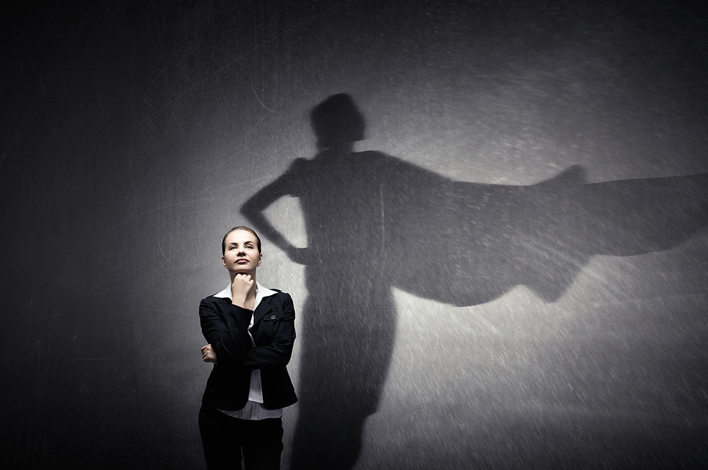 A confident businesswoman is shown. Her shadow is wearing a cape like superwoman.