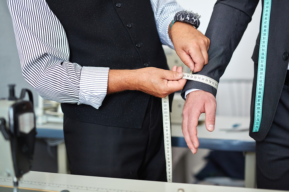 A tailor measures the arm of a businessman to make sure he has the perfect fitting suit.