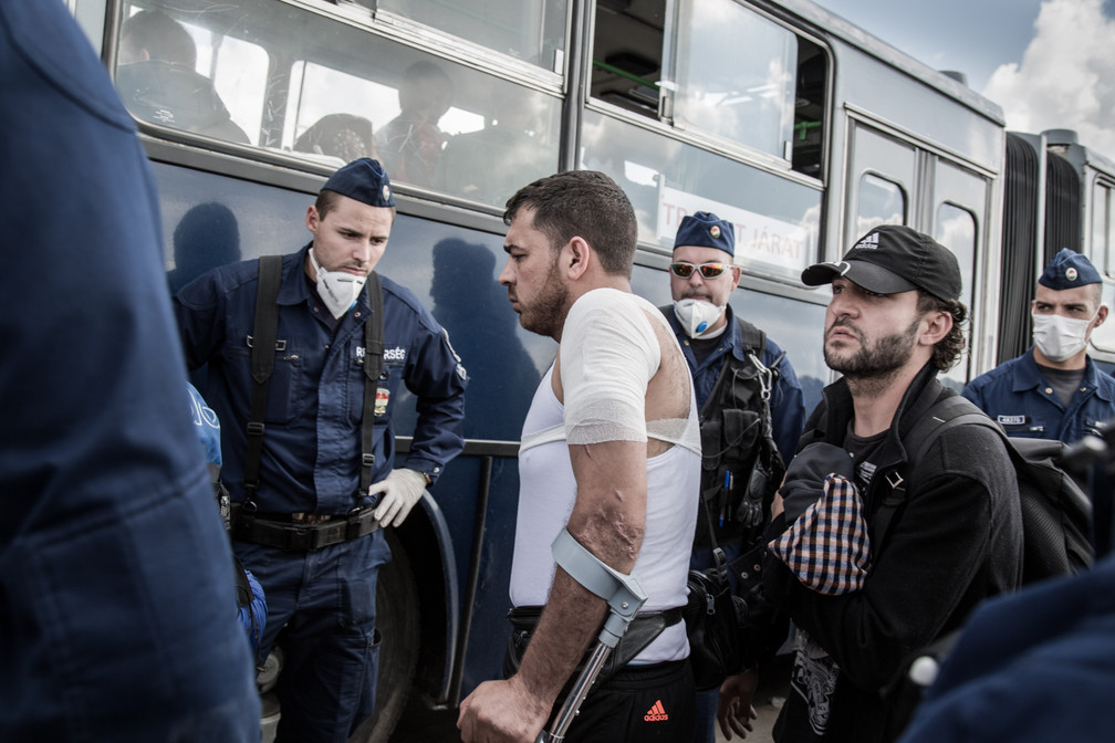 """Man wounded by a bomb in his home town in Syria boards a bus to a """"registration camp"""" in Roszke, Hungary."""
