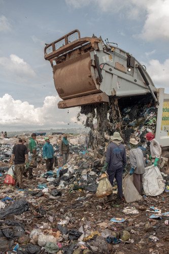 A truck carrying wet waste unloads in front of a group of scavengers, at the Estrutural dump in Brasilia, on Monday, Jan. 15, 2018.